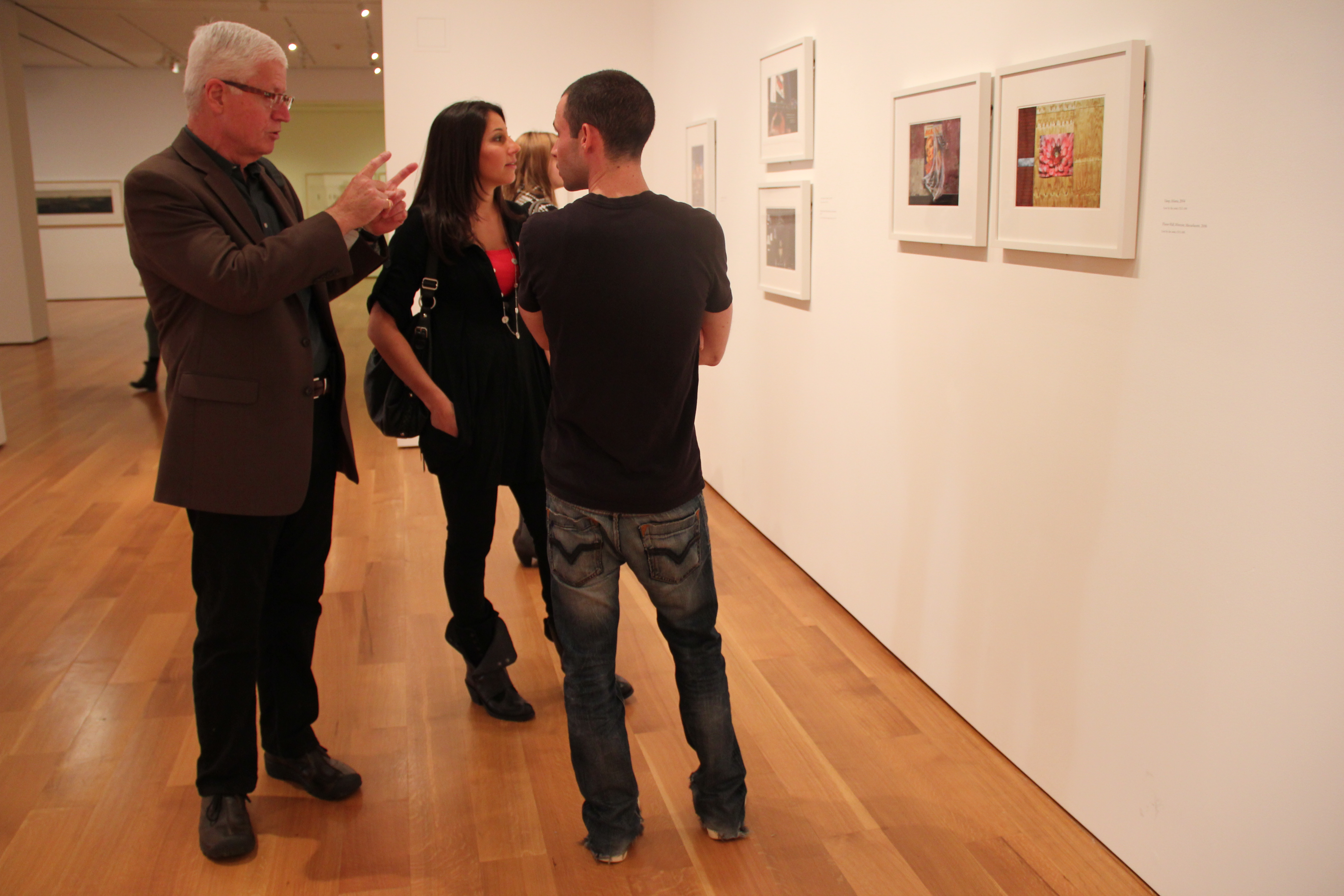 PHIELDING PHOTOGRAPHY QUESTIONS PHROM PHANS: Chip Simone answers questions from visitors at his exhibit, The Resonant Image, on the bottom floor of the High Museum.  Simone was often present at the High and frequently discussed his work  with the people who visited his show.