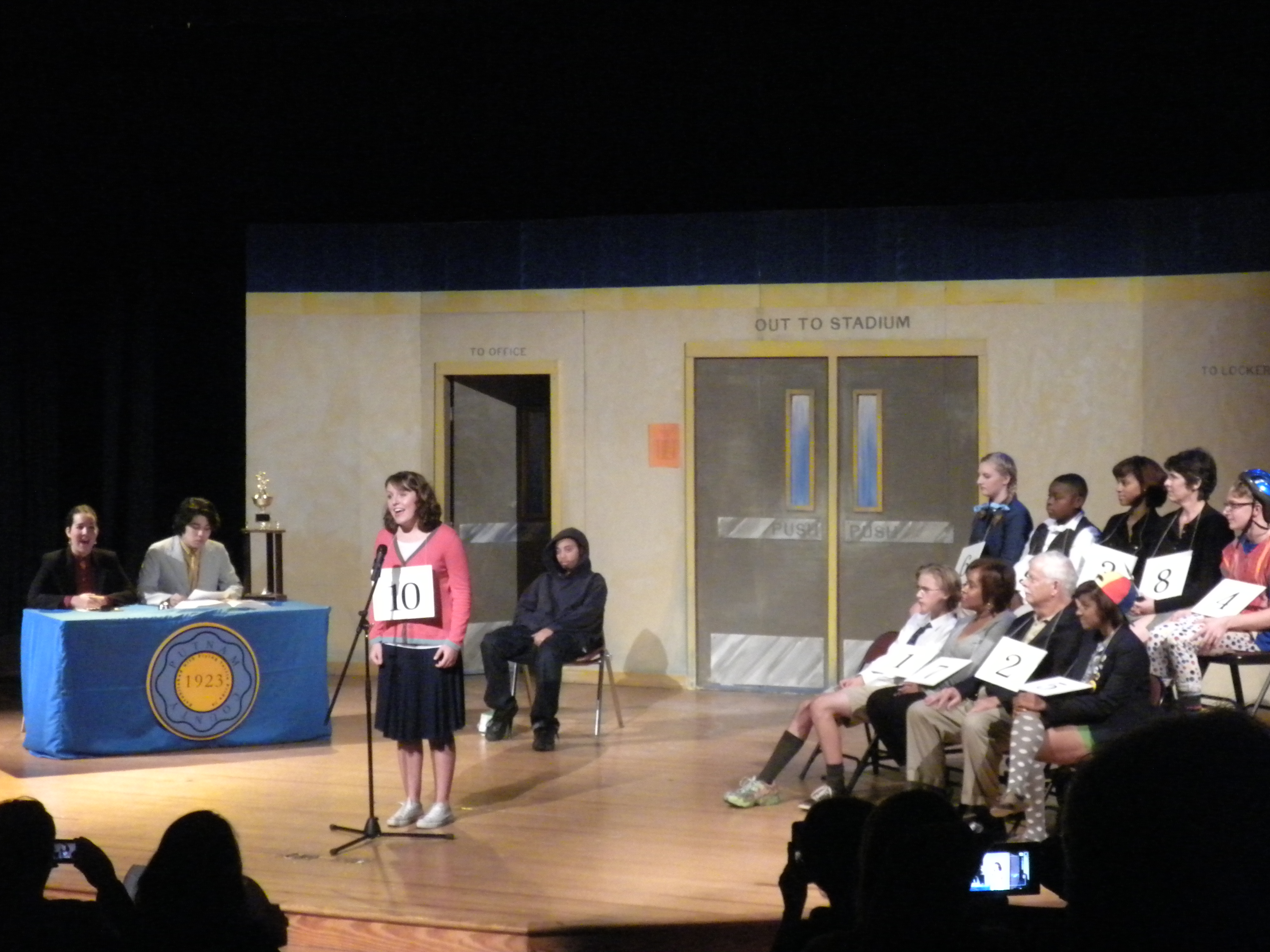 Junior Eliza Renner steps up to the microphone to put her spelling skills to the test as her character, Olive.