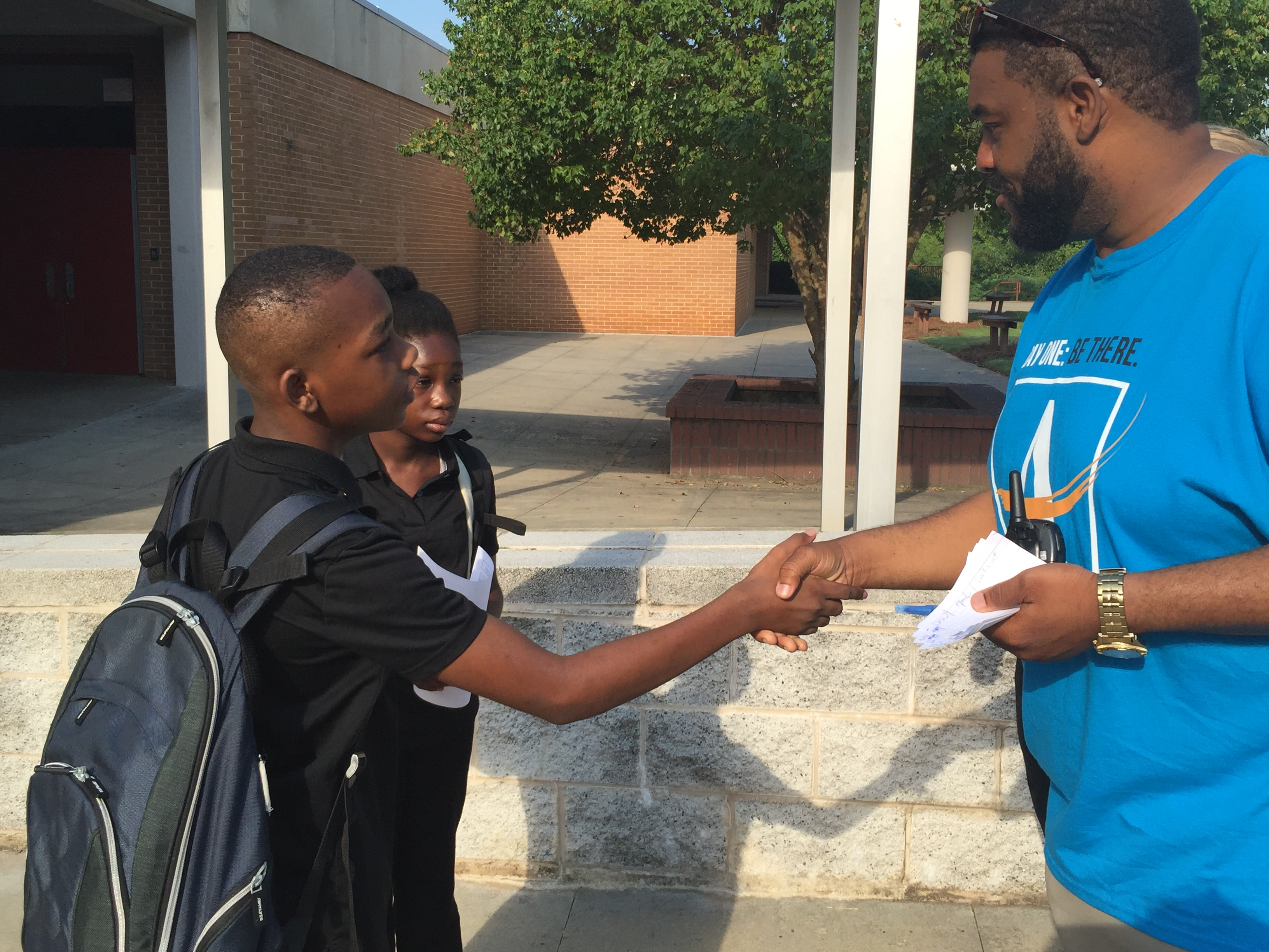 "SHAKING IT UP: Price Middle School Principal Duane Hale greets his new students on the way to class. Next school year, Purpose Built Schools of Atlanta, a local charter school corporation, will control Price Middle. Hale said the plan was ""perhaps the best alternative for all children in the Carver Cluster to be successful."""