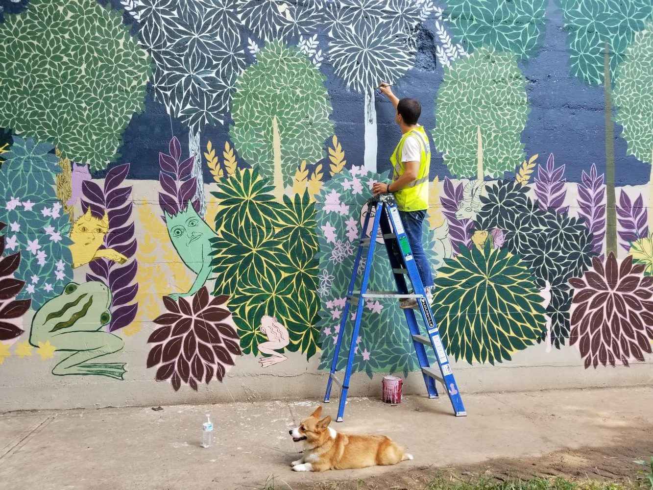 "ARTIST AT WORK:  Andrew Catanese, an Atlanta-based artist, works on his mural on the BeltLine beneath the Eastside Trail. Catanese paints murals in the ""horror vacui"" style. volunteer help."