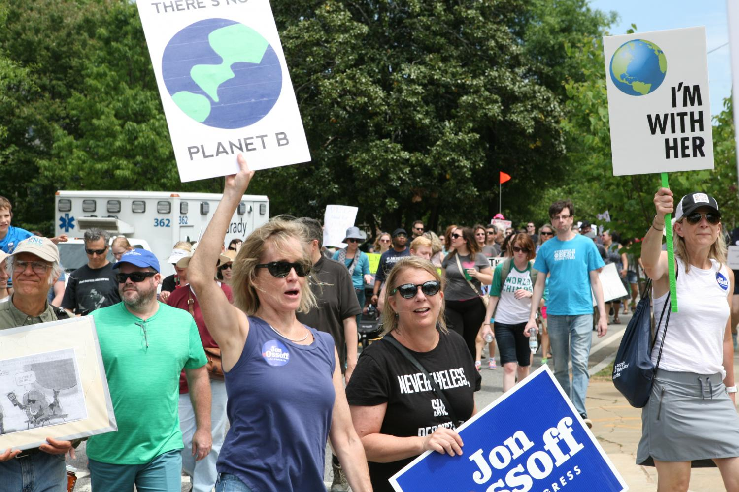 Marchers+turn+onto+Euclid+Ave+in+Candler+Park+carrying+signs+supporting+environmental+friendly+policy.+Some+marchers+took+a+more+political+stance%2C+carrying+signs+reading+supporting+Jon+Ossoff.+