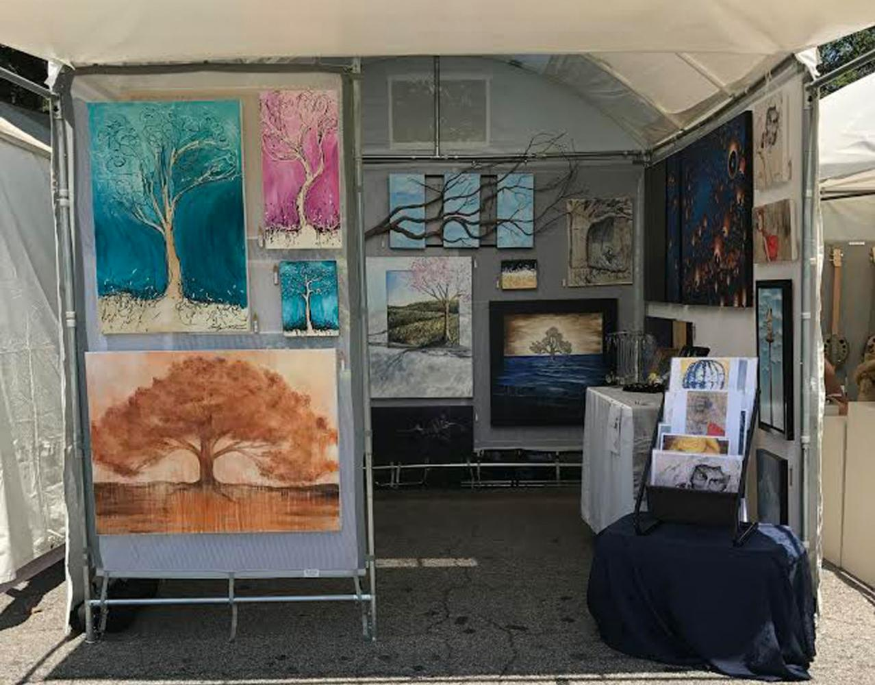 An artist displays his or her paintings at the Piedmont Park Arts Festival. Photo by Parker Killenberg.