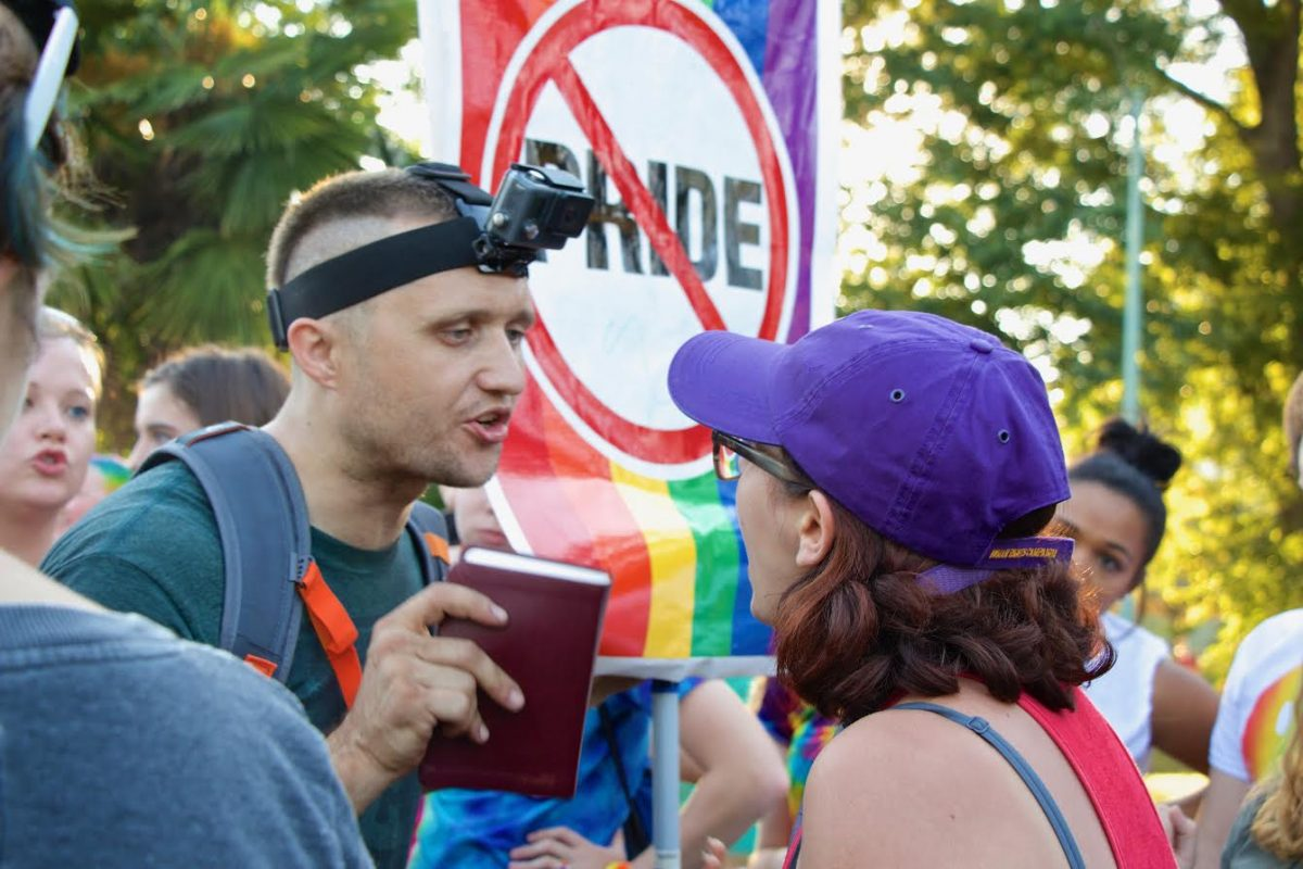 A group of protestors at Atlanta's annual Pride Festival in Piedmont Park confronts a festival-goer, one of whom has an anti-pride sign. Some Grady students have expressed that, while most students and teachers are accepting, they occasionally feel excluded or unable to be themselves.