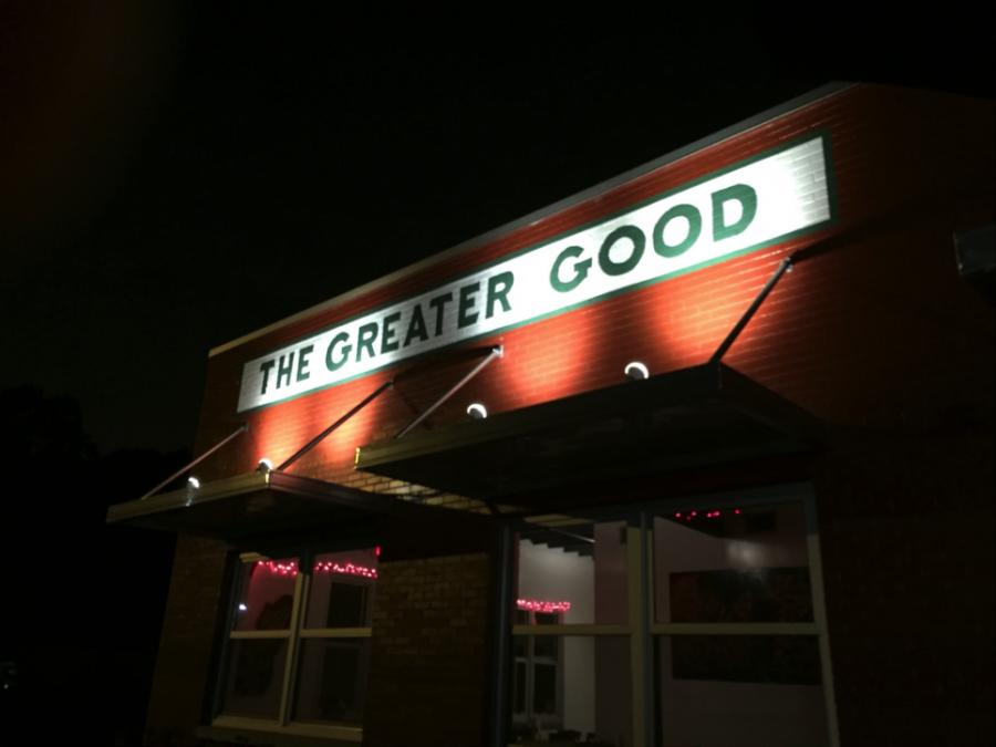 The greater Good BBQ sign illuminates the night.