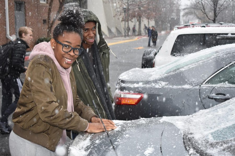 Students rake snow off of cars to create the perfect snowball.
