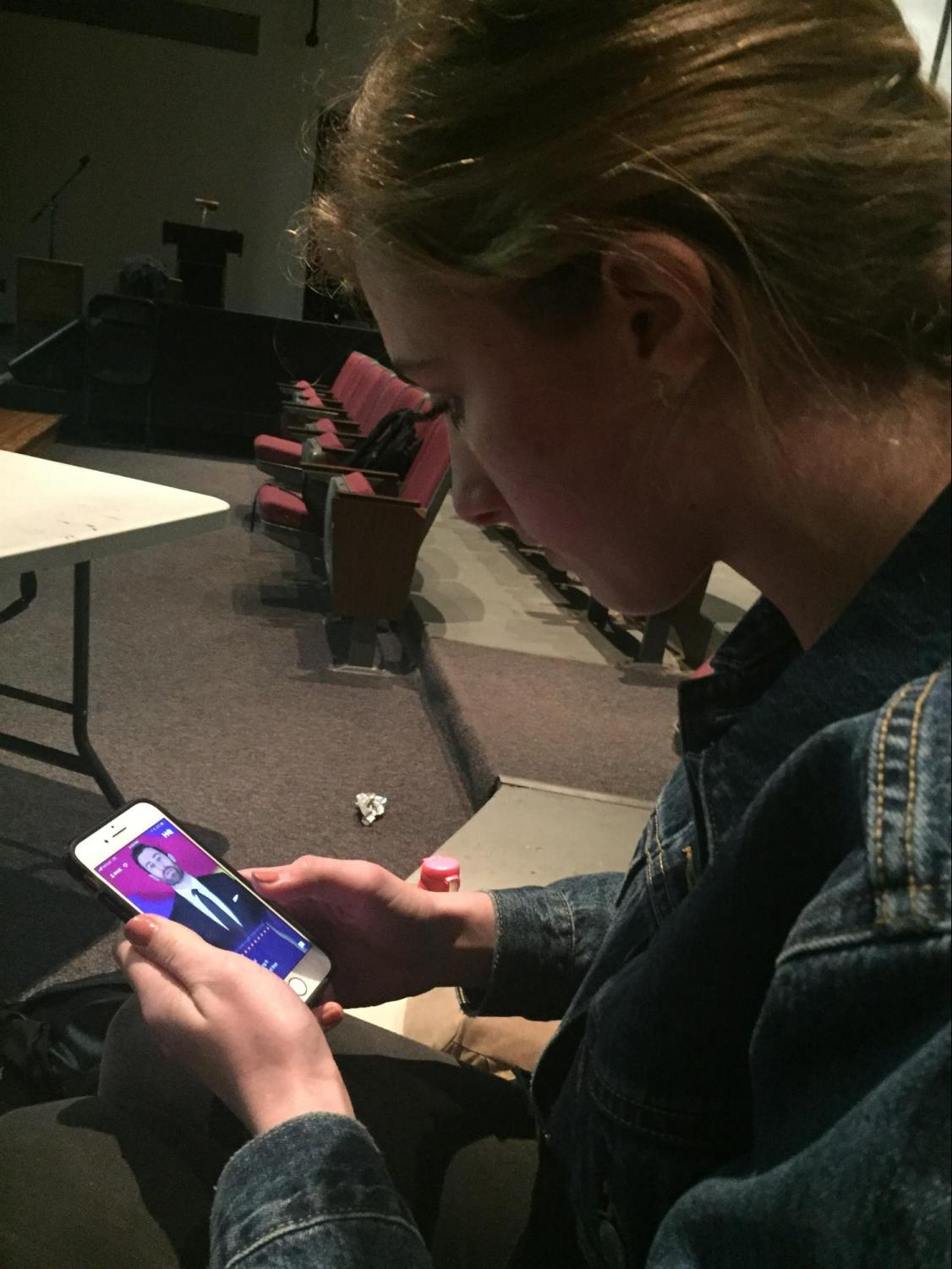 Junior Olivia Hunter pulls her phone out to play 'HQ' in the Vincent Murray Auditorium on Thursday, Jan 25, 2018. Hunter looks anxiously at the phone as Scott