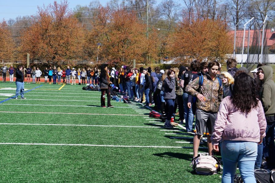 Students link arms on the field an hour after the organized walkout. After several students decided to remain on the field for further protest separate from administrative supervision, the group of additional protesters amassed to 200.