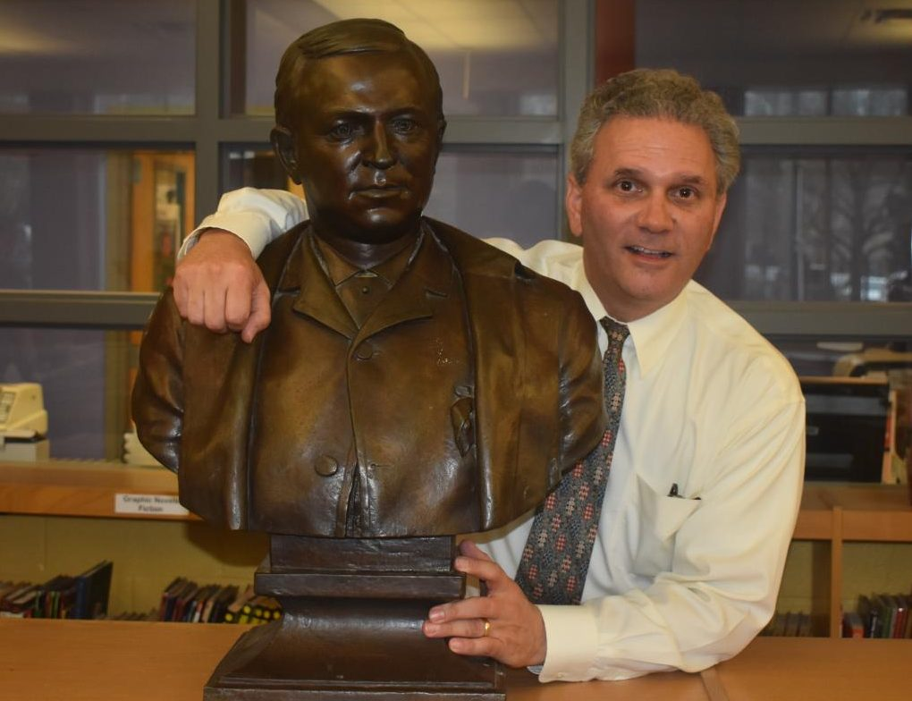 GENERATIONS OF GRADY: Henry Grady III stands with a bust of his great-great-grandfather, Henry W. Grady, after whom Grady High School is named. The bust is in the Grady library.