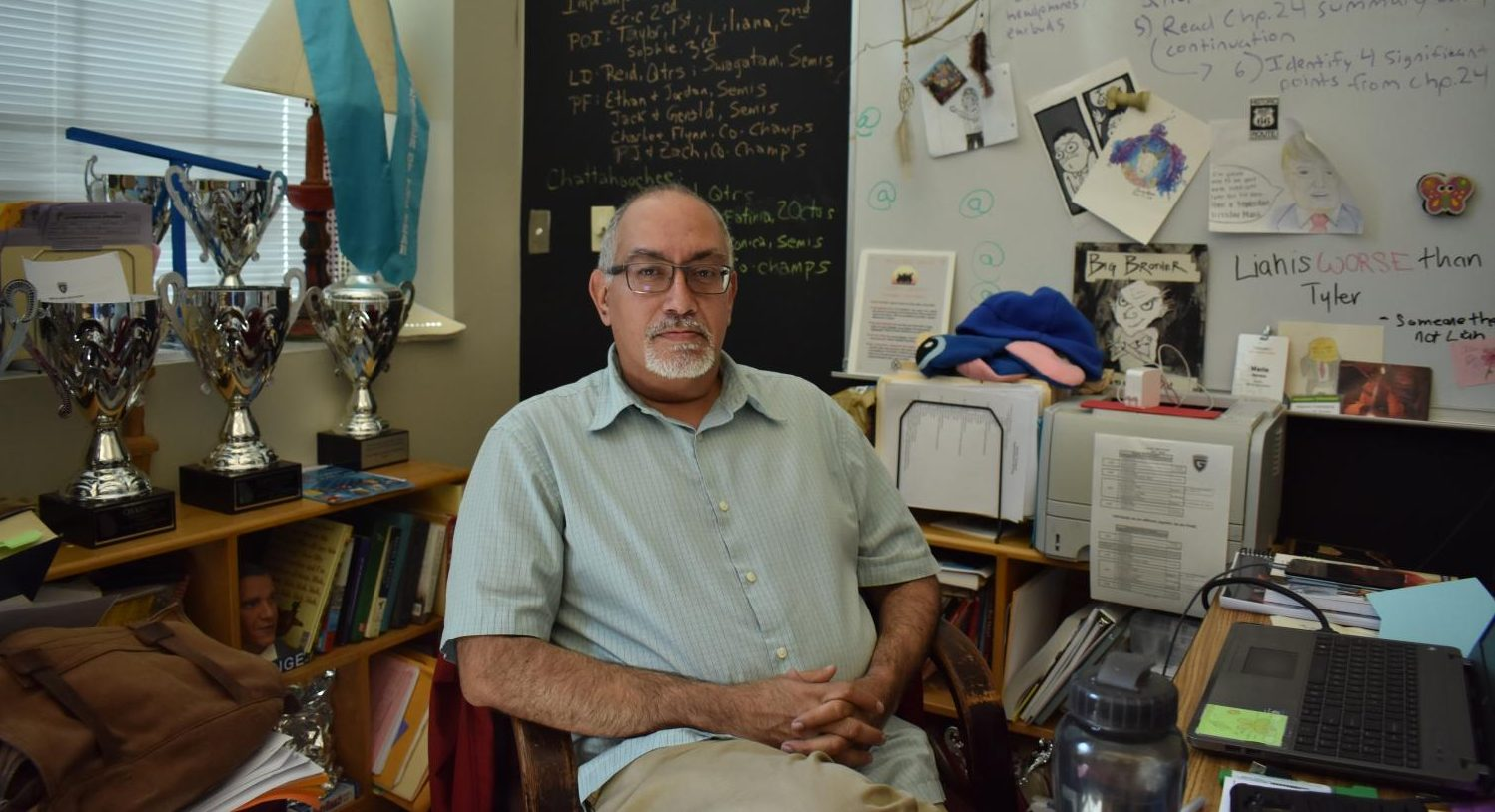 Mario Lorenzo Herrera sits in his iconic third floor classroom filled in view of hundreds of trophies and awards the debate team has won under his care.
