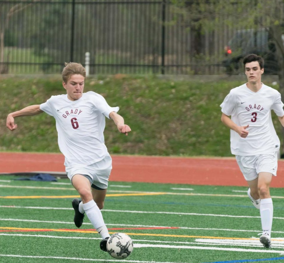 Senior Alex Westin kicks the ball as teammate junior Reid Fazenbaker trails him.