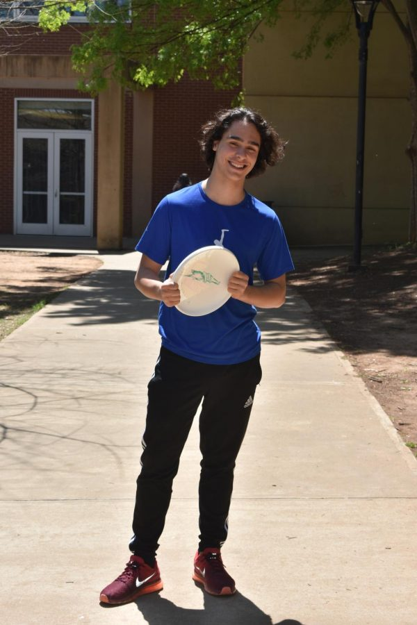 Junior Gomes-Johnson stands holding a frisbee, demonstrating his love for the sport.