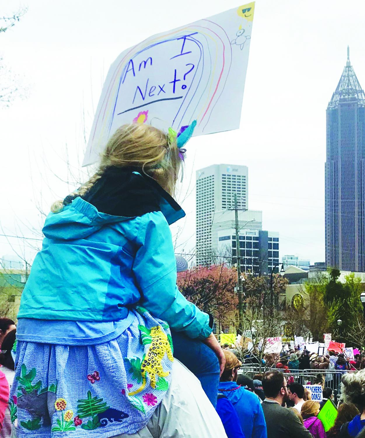 ON THE SHOULDERS OF CHANGE: A young girl sits on her father's shoulders while marching in Atlanta on Mar. 24 with a sign reading