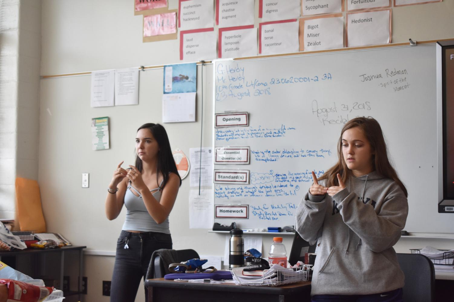 Juniors Liah Lawson (left) and Olivia Bransford teach sign language to members of the newly-created Sign Language Club.