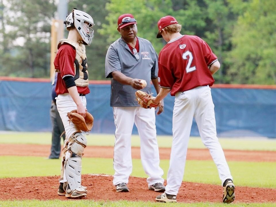 Coach Ron Killinsgsworth (center) confers with recently-graduated pitcher Luke Levens (right) and catcher Will McFarland (left) during a game in the 2017 baseball season.