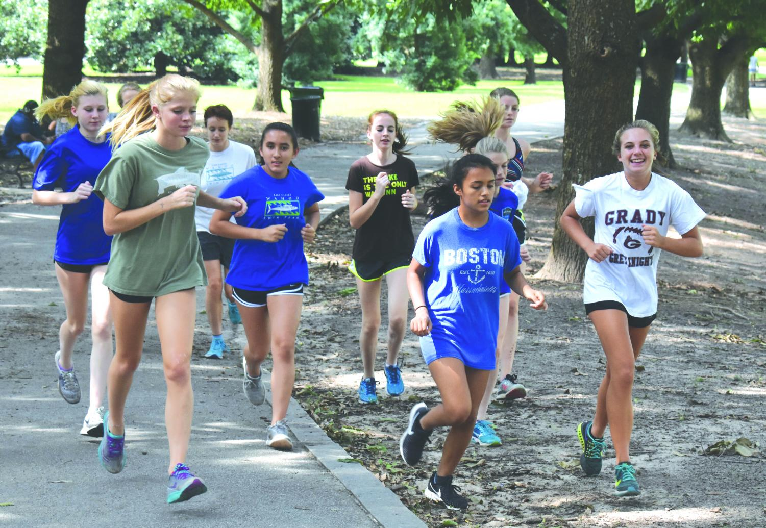 Speeding into the season: The girls cross country team runs through Piedmont Park during one of their afternoon training sessions.