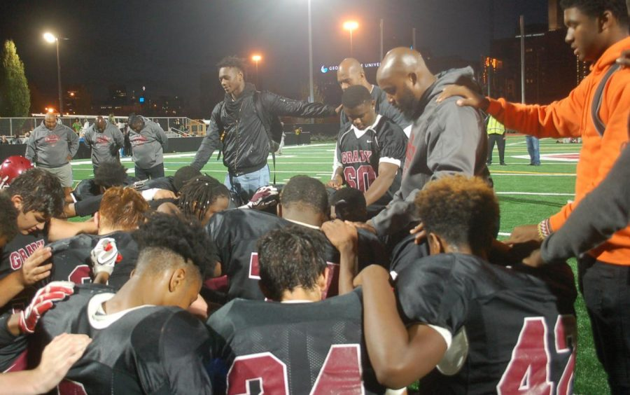 Coach+Anderson+leads+the+routine+post-game+prayer%2C+as+players+come+together+each+with+a+hand+on+another%27s+back.
