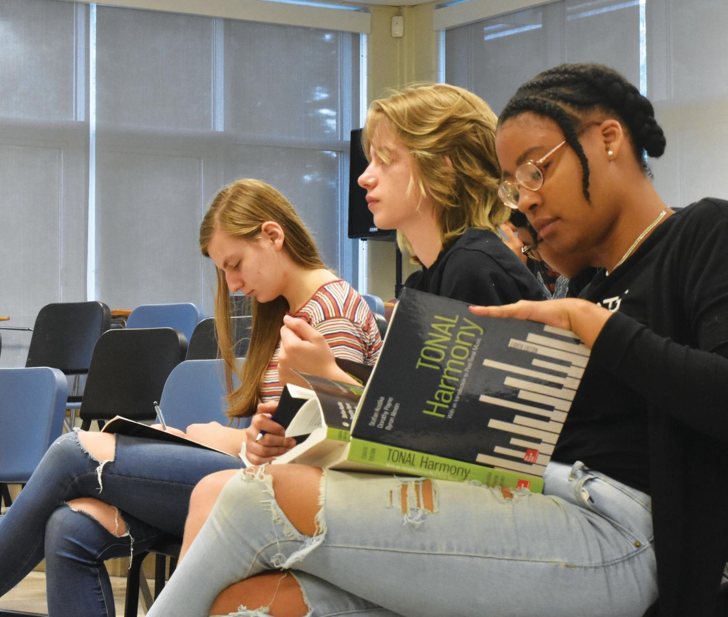 Senior Taylor Jackson, junior Gabby Nimmer and  senior Lucy Gelber look through their AP music theory books as Mr. Hill calls on students for answers.