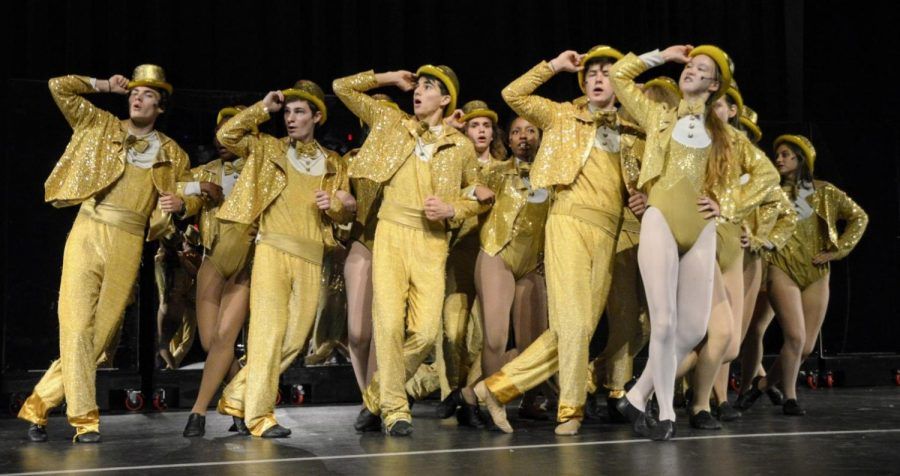 The original 17 members perform their final number, One in shiny gold costumes.