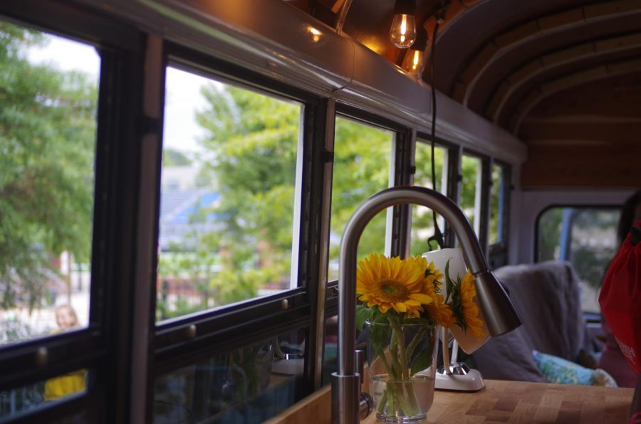 Sunflowers sit on the counter in a tiny home, converted from a school bus. The owner converted the entire bus himself but still finds that the home is a continuous piece of work.
