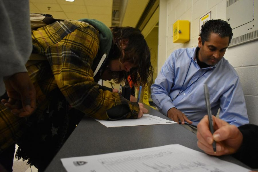 Administrators such as Byron Barnes help issue tardy slips to late students.