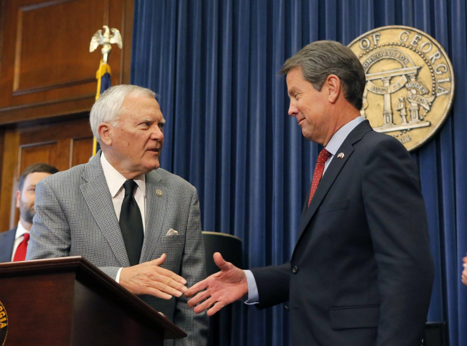 Former Secretary of State Brian Kemp (right) shakes hands with Georgia Governor Nathan Deal (left) on Nov. 8, as Kemp resigns from his position.