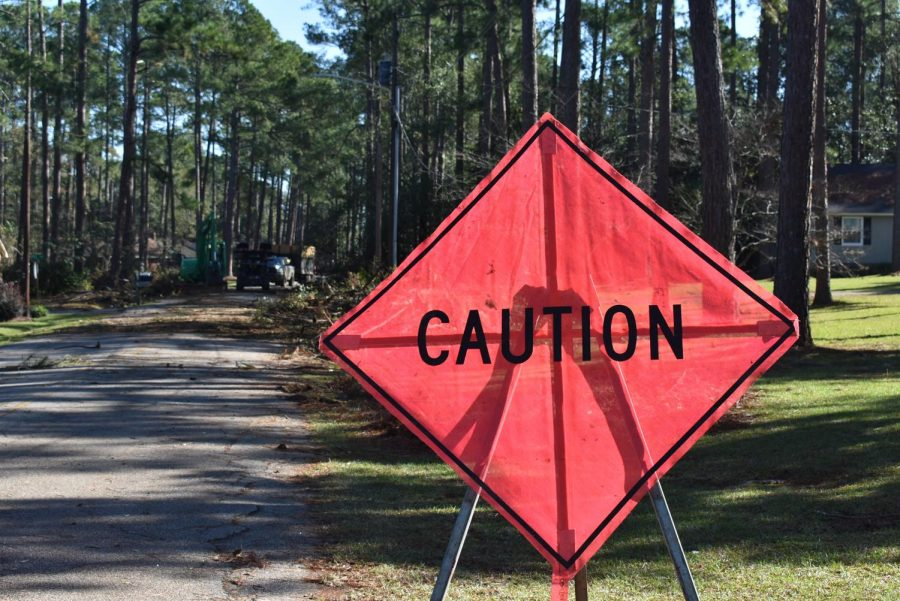 AN AIR OF CAUTION: A caution sign stands in front of FEMA crews cleaning up debris. Roads are blocked due to the amount of limbs and fallen trees the crew has to remove and break down.