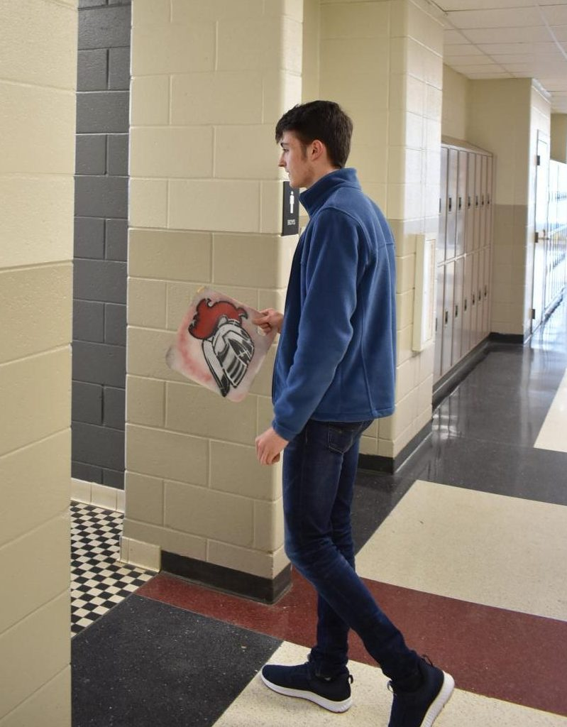 """Anything that goes into a restroom is super dirty, no matter what. I'm completely grossed out about it,"" said junior Isaac Turner, shown here carrying the pass into the restroom."