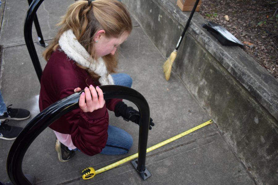 Junior Bria Brown led an initiative to bring 7 more bike racks to Grady this January. Freshman Nora Ball is pictured measuring distance between the rack and the border.