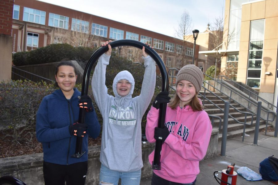 Students+smiling+as+they+are+halfway+through+bike+rack+installation.