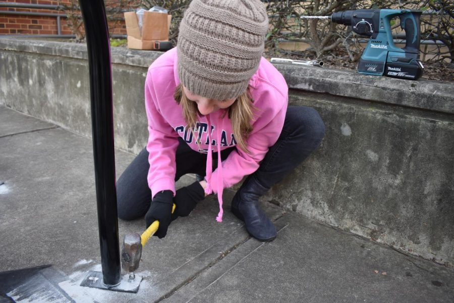 Freshman Ava Smith hammers in a nail as yet another bike rack is in the ground.