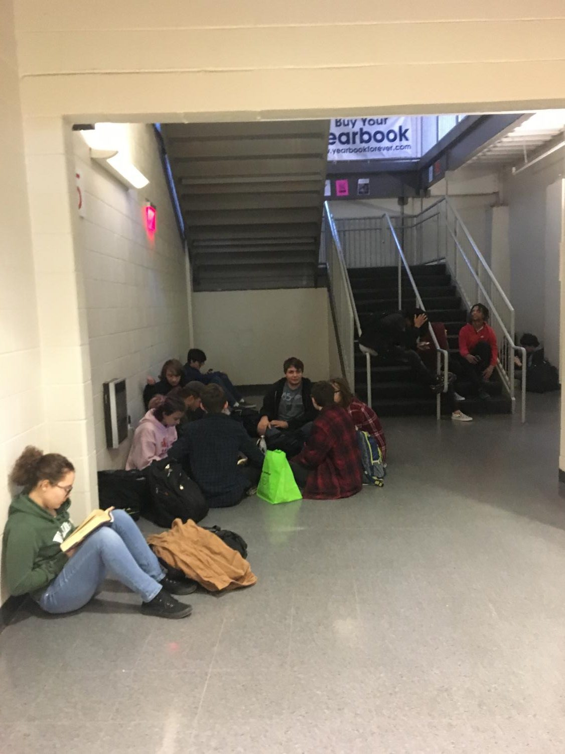 Students sit under the E Hall stairwell during the second lunch period. Not all students eat in the cafeteria. Many eat outside or use the time to prepare for class in the hallways, outside or the library.