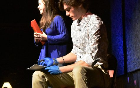 Nathaniel Ward writing on a piece of paper as sophomore Bianca Weber proclaims her love for him at Coffee House, an expose of Grady talent, on January 24, 2019.