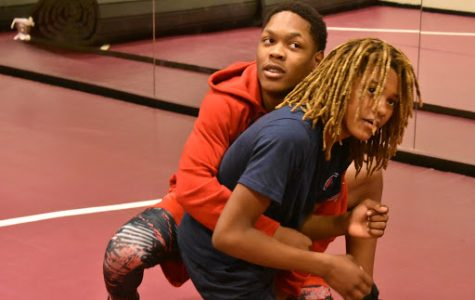 Freshmen Jakari Christian (left) and Malic Henderson (right) learn a new technique during wrestling practice. The team practices in the dance studio.