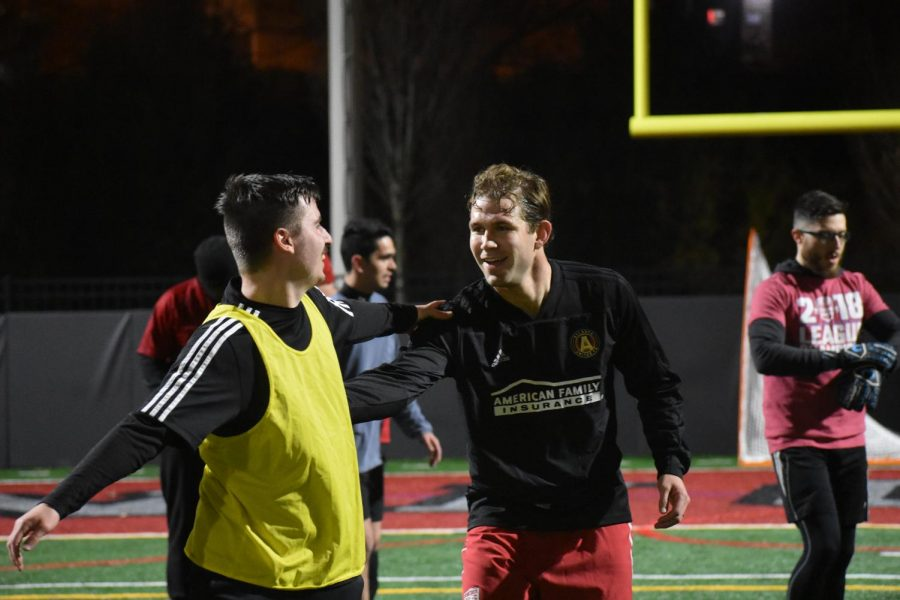 Players from Sons of Pitches' adult league shake hands as they congratulate each other on a game well played.