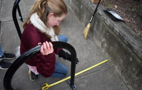 Freshman Nora Ball happily measuring the distance from the bike rack to the curb, so as to comply with City standards.
