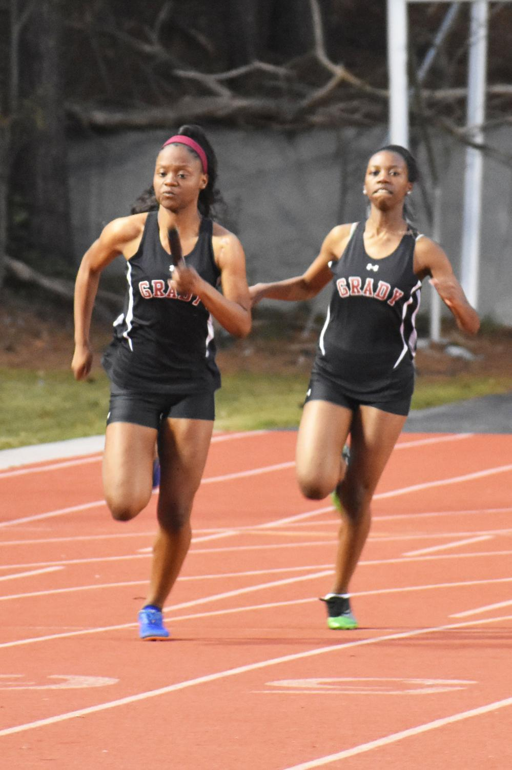 """Sophomore and captain Ameah Richardson receives the baton from sophomore Kendall Jones in the 4x100m relay  at the Grady Opener on Feb. 26. """"It felt really good to be named captain this year, and I really hope that I can meet the expectations of the team and bring us together more as a family than a team,"""" Richardson said."""