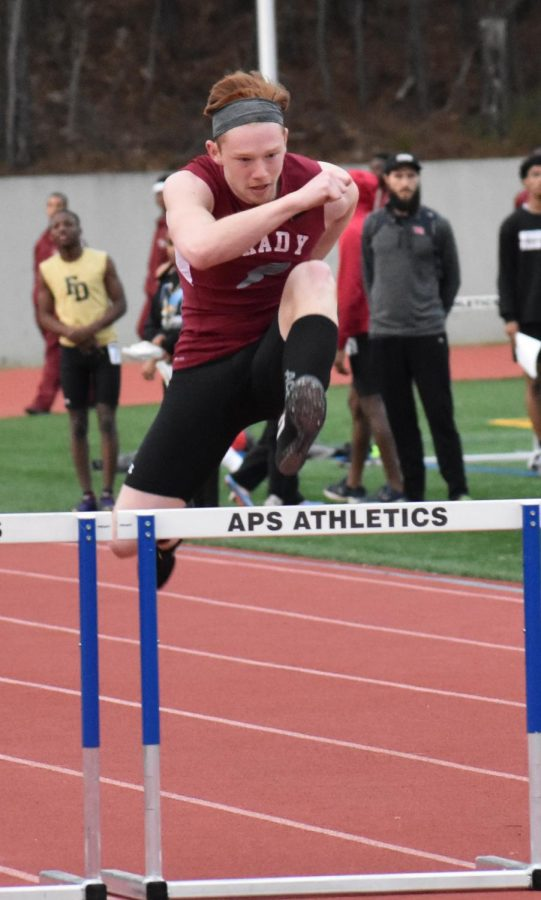 Sophomore Jackson Sexton jumps over a hurdle in the 300m hurdle race in the Grady Opener on Feb. 26. Sexton also runs the 400m dash in 50.2 seconds.