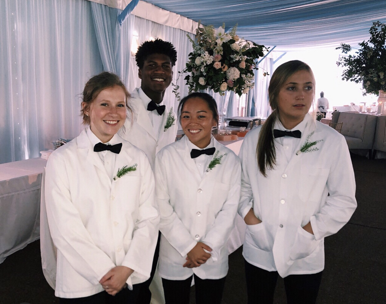 Alumni Melissa Drake, Camilla Kasper, and Georgia Smith (left to right) stand in front of senior Malachi Smith after setting up food for a wedding.