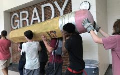 Tech theater students carried the pencil statue, symbolizing standardized testing, from the front lawn to the scene shop on Friday, August 23.