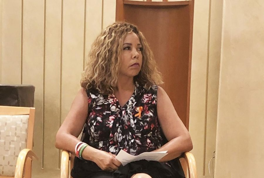 Congresswoman Lucy McBath quietly sits while she  listens to student-activist Ethan Asher speak about gun violence in schools.