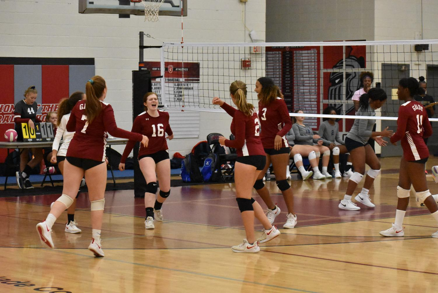 Senior Sadie Mothershed celebrates with her team after getting a point from a spike on the previous play against Locust Grove on August 28. The Lady Knights lost 2-1.