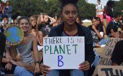 Junior Amarie Blackshear, listens to a speech from Danielle Millburn, as she holds a sign reading: