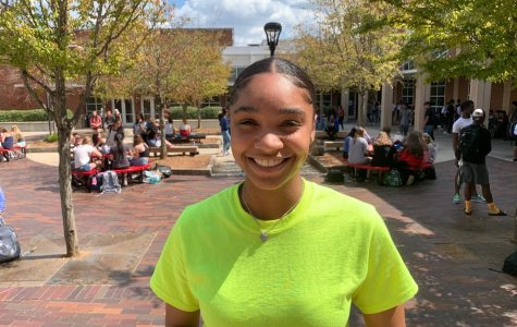 Taylor Spencer, a candidate for Executive President, smiles as she stands in the courtyard.