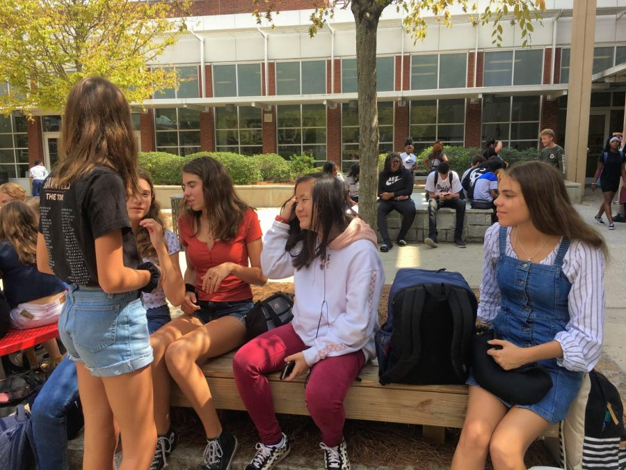 NO BOYS ALLOWED: An all girls friend group sits together outside during lunch without any boys.