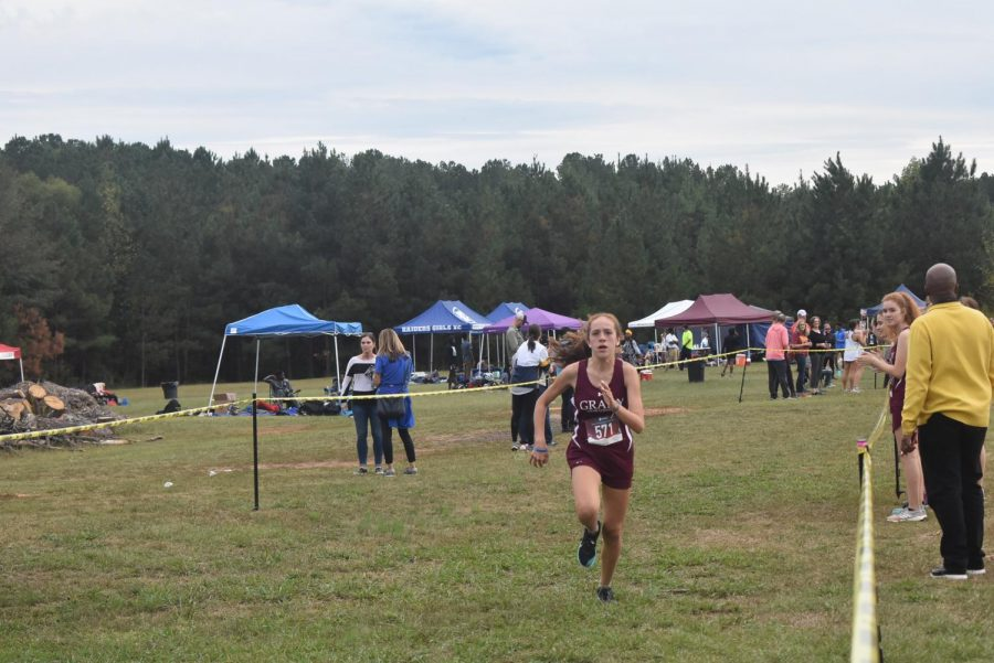 Freshman Emilia Weinrobe strides to the finish line. She finished 5th in the girls Varsity race.