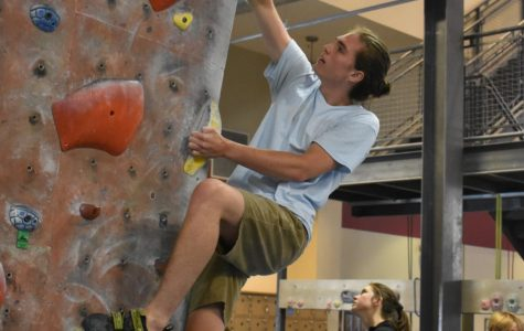 Senior Will Meyer climbs a bouldering route at Stone Summit before his shift starts. Meyer has been climbing since 9th grade, and is planning on going on a climbing trip to a cliff in Kentucky with fellow employees.