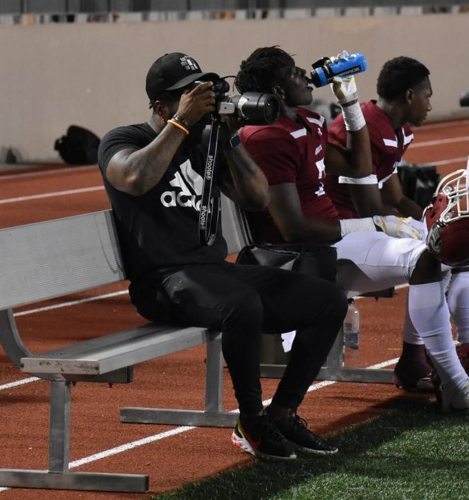 Former Grady quarterback Simeon Kelley (left) focuses the camera on the action from the bench as senior tight end Dewan Wright (center) squeezes a swig of water and current quarterback and senior Aquinas Stillwell (right) takes a breather. Kelley, now a photographer for Atlanta Public Schools, led the Knights to an undefeated regular season and state semifinals finish in 2005.
