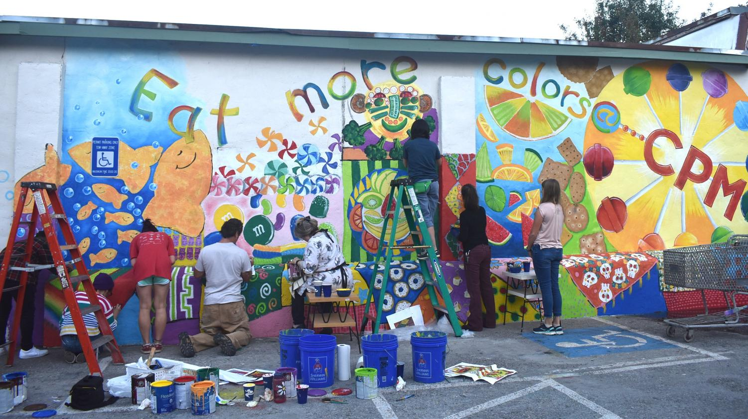 Grady Cluster teachers and students paint community mural on the wall of the Candler Park Market.