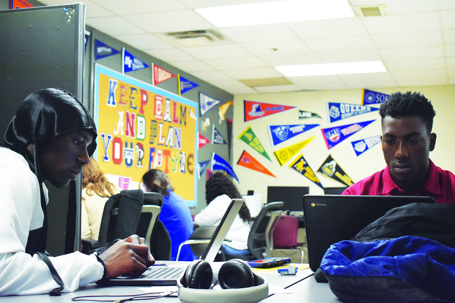 Seniors Melik Etienne (left) and Jason Nolton (right) spend third period working with college advisors Amber Jones and Abby Poirier in the college advisors' office. On the wall is a a message reading