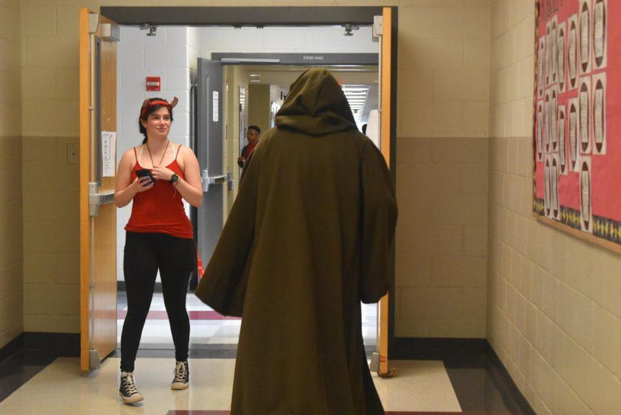 Grady Speech & Debate coach Mario Herrera in Jedi attire turns heads as he passes senior Hope Nathanson dressed as a devil in the hallway.